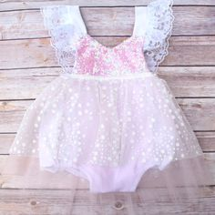 Beautiful full tutu dress and romper with a winter elegant theme. This listing is for the Limited Edition Holiday Sparkle Romper® only. The sequin top is a halter featuring flutter sleeves. The neck t