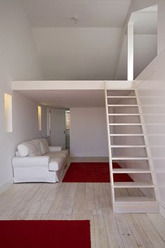This small apartment has a lot more to it than meets the eye. It may look like just a plain living area, but there are multiple hidden doors for maximum storage and aesthetics. The downstairs features a hidden bathroom and a small living room area. The upstairs has an attic area and a bedroom with plenty of usable space. They used a bright white color for the walls to enhance the light coming in because of the size of the area and it does a great job.