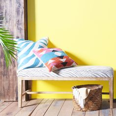 Bring the sunshine inside with a bright accent wall and pops of colorful fabric.