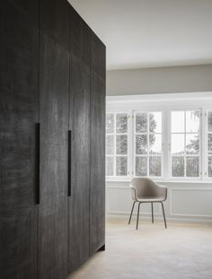 The Historic Villa Once Home to Poul Henningsen Receives a Modern Renovation - Photo 2 of 12 - A large kitchen cabinet covered in dark stained oak separates the kitchen from the living room.