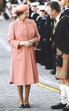 1985 from Queen Elizabeth II's Royal Style Through the Years  The Queen stepped out in a salmon pink frock (featuring her signature A-line silhouette) and hat ensemble.