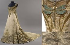 """This work of art is """"Bord de rivière au printemps"""" - Riverside in Spring - and was designed by the French architect, painter and sculptor, Victor Prouvé. The dress was likely created in 1900 or 1901, and was put on display at the Salon de la Sociéte National des Beaux-Arts. The piece uses beautiful details and embroidery depicting the theme of Spring. It can still be seen on display at The Musée de l'École de Nancy in Lorraine."""