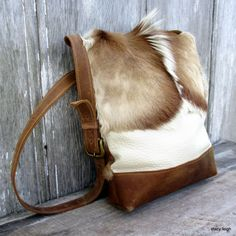 Very soft, Springbok, hair on bag combined with off white leather. The bottom of the bag is made from distressed brown leather. The flat strap is long…