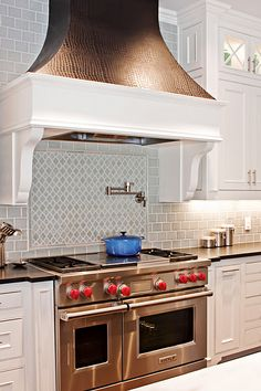 Love the soft color of the backsplash with this great copper colored faux croc skin on the vent hood.