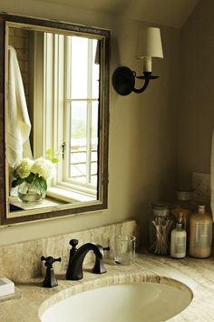 Rustic country bathroom features beveled mirror illuminated by oil-rubbed bronze sconce over stone ...