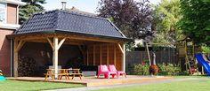 #grote #overkapping op een #verhoogde #houten #vlonder met #loungebanken #picknicktafel #ligstoelen #buitenhaard en ernaast #speeltoestellen. #Kindvriendelijke #tuin | Heart for Gardens.