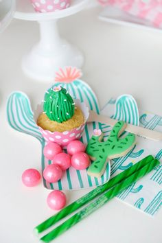 Cactus themed children's birthday party desserts. Cactus cupcake, cactus cookie, pink and green candy. Matching cactus paper plate and napkin. Cactus Party styling by Happy Wish Company. Photography by Tammy Hughes Photography. Stationery by Minted artist, Baumbirdy.