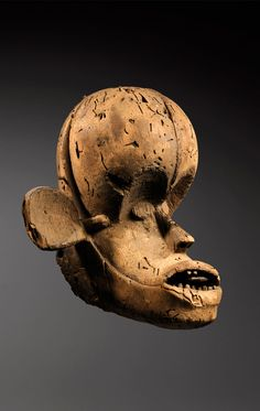 Africa | An dance crest head from the Ekoi people Cross River Region of Nigeria | Wood; natural patina, giving a clear indication that it was originally covered with skin, fixed by wood pegs at the back of the head.  The holes at the base were most likely used to attached the wicker base