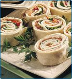 "simple turkey roll-ups -- lay out a whole grain tortilla, smear thin layer of garden vegetable cream cheese, lay out turkey and fresh baby spinach leaves, then roll up.  Slice ""tube"" into bite size wheels."