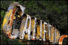 Part of an old hotel sign resting behind chain-link fence near Griffith Park. The sign was from the Hotel Californian. Photo by Jody Miller.