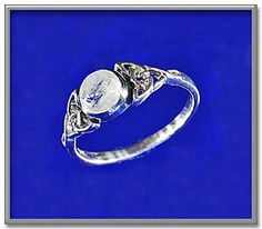 """Moonstone Celtic Ring - Capture the magic of the full moon with this delicate silver ring, with a rainbow moonstone cabochon set between two Celtic knots. Gemstone moon measures 1/4"""" in diameter."""