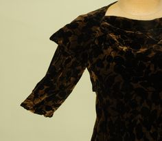 Arm Detail VOIDED VELVET and GOLD BIAS CUT EVENING GOWN, c. 1930. Black velvet in an overall pattern of cherries on a metallic gold ground with draped cutout V-back with four self button and loop closures at top, slight cowl front, pointed cap sleeve and unusual looped arm treatment.