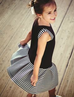Narrow stripes add a sporty, playful touch to the girly styling of the Navy Blue Striped Dress. Made from viscose/poly/spandex, this adorable design features a sleeveless top with a round neckline, striped accents at the shoulders, and a pleated striped skirt in a flared A-line silhouette. See more children's clothes at DeuxParDeux.com // Deux Par Deux // kids clothes // kid style // fashion for kids