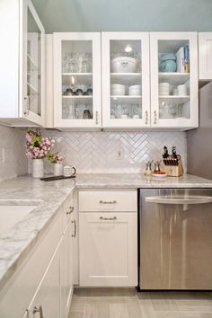 This light and bright modern kitchen combines white and gray tones to create a lively area of the home. Glass front cabinets are mixed in with white Shaker style cabinets, while a gray and white marble countertop offers a finishing touch. A white tile herringbone backsplash adds fun texture to the space.