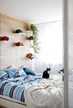 Smart use of space in the bedroom includes shelves behind the bed and underbed storage