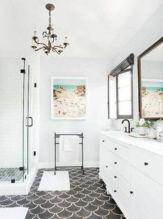 Gorgeous contemporary bathroom with fish scale floor tiles and a bronze chandelier.