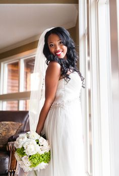 """Brides.com: A Lakefront Summer Wedding in Stilwell, Kansas. The bride's Emily Hart Bridal gown featured a rhinestone detail that wrapped around her waist. Leah describes its short train as a """"tail."""" Her Emily Hart Bridal veil was embellished with a beaded floral detail."""