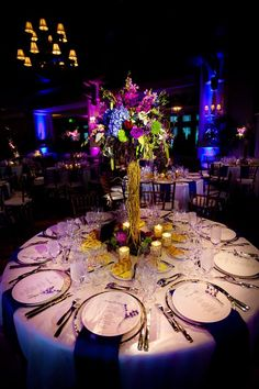 Tall centerpieces decorated with twisg and blue and purple flowers