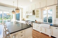 A chef might feel right at home in this bright, white eat-in kitchen. Featuring an island with barstool seating, mirrored globe lighting and a farmhouse sink -- plus plenty of cabinet storage space -- this space welcomes families and festive gatherings alike.