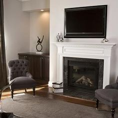 HGTV - living rooms - fireplace tv niche, tv niche over fireplace, tv niche above fireplace, black marble fireplace surround, brown tufted chairs, chairs on caster legs, brown rug, , Gloria Chair,