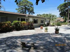 Front of house showing  shell driveway off front patio with parking for 2 cars.