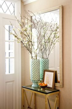 Love this table/entryway arrangement, large mirror above console, Greek key framed mirror, cream Greek key mirror, cherry blossoms in vase, aqua blue vase, gilt frame, gold console table, gold console table with black granite top, gold x sided console table, entryway vignettes, styling a small entryway