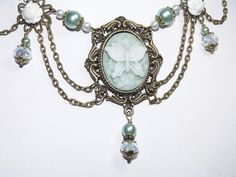 Victorian Teal and White Floral Butterfly Cameo with  Antique Brass Necklace. $29.95, via Etsy.