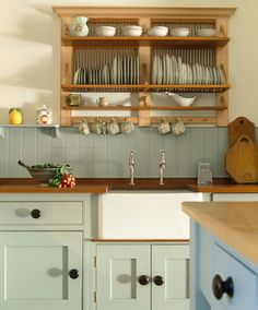 Stock Photo: 4291-15297 Wooden plate rack above white Belfast sink in kitchen with pale green fitted units