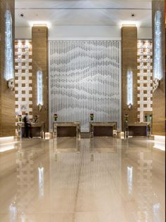 'Drift', a sculptural artwork for the lobby of the Kempinski Hotel, Dubai by Giles Miller Studio.   Thousands of boxes of varying depths are suspended in front of a wall and lit in such a way that they cast varying degrees of shadow on the wall behind.