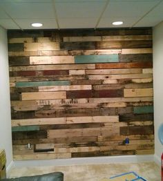 Pallet wall in our basement! We added some teal blue slabs to the mix. Maybe a copper cocktail rail ? My best tip is to paint the drywall a dark color prior to pallet install. It disguises blemishes in the wood. Mark your studs and make sure to nail righ Diy Pallet Wall, Diy Pallet Projects, Home Projects, Blue Pallets, Wood Pallets, 3d Design, Wall Design, Artis Wall, Home Theater Installation
