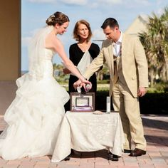 The couple performed a sand ceremony at the altar during their ceremony. The purple and white sand represents not only the unity of their relationship, but also the blending of their families into one. - Image Credit: Ailyn La Torre Photography