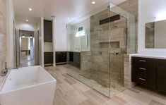 Contemporary master bathroom large glass shower with limestone tile dark wood vanity and freestanding tub