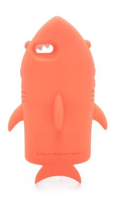 A soft silicone Stella McCartney phone case in the shape of a shark. Formfitting construction with button, cord, and camera access.  Fits iPhone 6 & iPhone 6s.