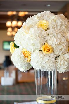 White hydrangea and yellow rose wedding reception centerpieces.
