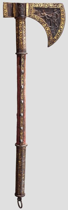 A chiselled and gold-inlaid Persian battle axe (tabarzin), 18th/19th century Solid blade with semi-circular edge, chiselled on both sides in hunting relief and with gold-inlaid decoration. On the socket and hammer head an Arabic inscription chiselled in relief. Velvet covered wood haft with two octagonal, ornamental gold-inlaid iron mounts, suspension ring attached to the handle. Gold-inlay partially somewhat rubbed and soiled, clearly improvable by cleaning. Length 56 cm.