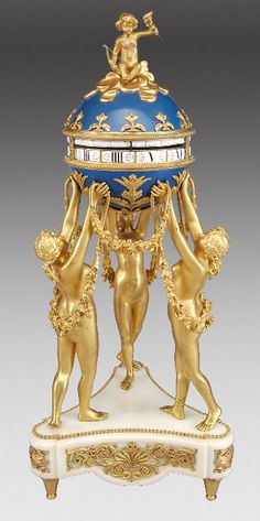 "112: French 'Three Graces' annular dial clock, the : Lot 112 bronze and marble clock, with Roi-de-bleu enamel globe surmounted by Cupid and 12 fleur-de-lis gilt mounts enclosing the two horizontal chapter rings, rack drive, bell strike stamped 5013. The globe raised by three gilt maidens with swaged laurels standing on a white concave marble base with inset pierced foliate panels raised on tapered feet. 25.5""H, Circa - 1880."