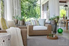 Detail of weather resistant armchairs with custom outdoor pillows and custom outdoor sheers. Ceramic garden stool, seagrass basket with Moroccan glasses and French decanter. Stark Carpet custom outdoor rug. Designer: Barbara Elza Hirsch of Elza B. Design, Inc. Photo: Greg Premru