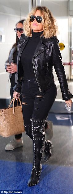 She showcased her curves in skintight ripped black jeans and lycra bodysuit...