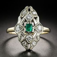 Something different and a bit more colorful in a classic Art Deco dinner ring. In place of the usual white diamond, a bright and lively green emerald-cut emerald glistens from the center of the geometric, diamond studded white gold top. The currently size 9 ring shank is rendered in sturdy, contrasting 10K yellow gold. Just shy of 7/8 inch.
