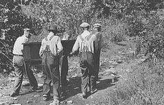 Original photo caption reads: Mountain people carrying a homemade coffin up creek bed to the family plot on the hillside where it will be buried. This section is too isolated to hold any formal funeral services immediately. Up South Fork of the Kentucky River near Jackson, Kentucky.