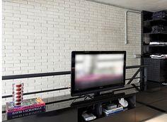 O closet e o cantinho da TV no quarto seguem a mesma linha do resto do apê, com muitos tons escuros (Foto: Divulgação)