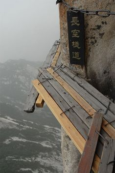 "The ""South Heavenly Gate"" which has 3 planks that you can balance on while holding on to a big chain that will keep you close to the cliff walls so you don't fall. Located in the Yellow Mountains of Huangshan, China."