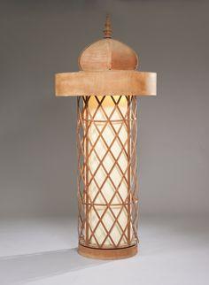 Jean ROYERE (1902 - 1981). Colonne Morris, le chapiteau surmonté d'une flamme stylisée, le fût cylindrique, rotatif, éclairé derrière un rhodoïd de couleur ivoire inséré dans une claustra, base ronde. Hauteur : 243 cm.