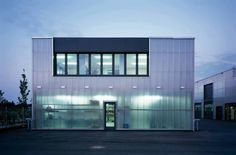Maintenance Facility / Allmann Sattler Wappner Architekten. A surprisingly ephemeral building has been created due to the translucent, heat- insulating polycarbonate facade, the reinforced concrete construction is faintly visible from the outside and the workshops bathed in daylight.