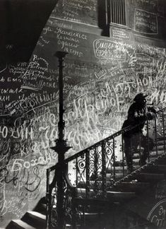A Russian soldier in the Reichstag surrounded by walls covered in Russian graffiti.