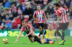 Lee Cattermole of Sunderland is brought down by...