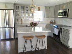 Zentrum der Aufmerksamkeit in dieser weißen und grauen Küche ist die Marmorküche Bar schöner mit einer Vase voller Blumen.