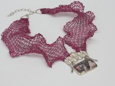 by Linda Magi. Magenta knit necklace with porcelain jasper Formed, forged and wrapped argentium silver and fine silver pendant with bezel set Porcelain jasper suspended from knit lace. Hand knit from wool and stainless steel yarn and linen stainless steel yarn.