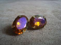 Brinco em base de metal dourado com aplicação de resina ovalada âmbar furta-cor (reflexos em roxo). R$26,00