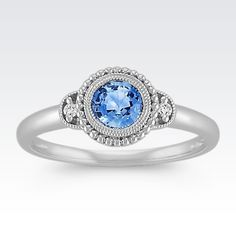 This brilliant vintage inspired fashion ring is crafted from quality 14 karat white gold. One vibrant Kentucky blue sapphire (approx. .53 carat) is surrounded by 12 round diamonds (approx. .03 carat TW). The milgrain detailing adds texture to the design and the total gem weight is approximately .56 carat.